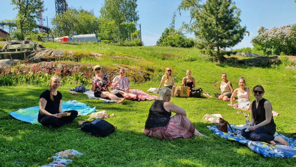 Kuvassa on Naistenkartanon henkilöstö kesäisellä lounaspiknikillä puistossa